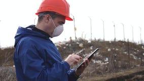 Το πρόσωπο στο κράνος και την αναπνευστική συσκευή ελέγχει τα απόβλητα για τη μόλυνση χρησιμοποιώντας μια ταμπλέτα Περιβαλλοντική απόθεμα βίντεο