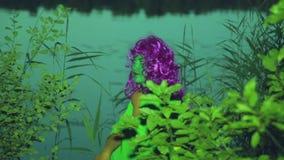 Το πρόσωπο της πράσινης μάγισσας που βγαίνει από τους θάμνους στην ακτή της λίμνης στο σούρουπο και κοιτάζει ήπια γύρω απόθεμα βίντεο