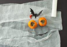 Το πρόσωπο του επιδέσμου και persimmon στο μαύρο υπόβαθρο με το ποντίκι ακτίνων Στοκ Εικόνες