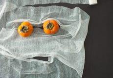 Το πρόσωπο του επιδέσμου και persimmon στο μαύρο υπόβαθρο Στοκ Εικόνα