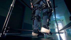 Το πρόσωπο φορά την ορθοπεδική ρομποτική συσκευή εκπαιδευτικό σε ένα νοσοκομείο 4K απόθεμα βίντεο