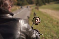 Το πρόσωπο χαμόγελου του όμορφου γενειοφόρου ευτυχούς ποδηλάτη στα σκοτεινά γυαλιά ηλίου απεικόνισε στον καθρέφτη μοτοσικλετών στοκ φωτογραφία