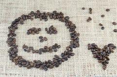 Το πρόσωπο Smiley και η μορφή καρδιών έκαναν εξ ολοκλήρου από τα σιτάρια καφέ Στοκ Εικόνες