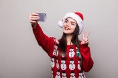 Το πρότυπα καπέλο santa ένδυσης κοριτσιών και το πουλόβερ Χριστουγέννων παίρνουν selfie Στοκ εικόνα με δικαίωμα ελεύθερης χρήσης
