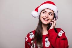 το πρότυπα καπέλο santa ένδυσης κοριτσιών και το πουλόβερ Χριστουγέννων μιλούν στο τηλέφωνο Στοκ Φωτογραφία