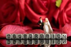 Το πρότυπο γαμήλιο ζεύγος με τον εορτασμό λέξης στις χάντρες και αυξήθηκε ανθοδέσμη Στοκ Φωτογραφίες
