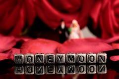 Το πρότυπο γαμήλιο ζεύγος με το μήνα του μέλιτος λέξης στις χάντρες και αυξήθηκε ανθοδέσμη Στοκ Εικόνες