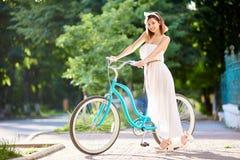 Το πρότυπο θέτει με το μπλε εκλεκτής ποιότητας ποδήλατο σε μια οδό πόλεων στοκ εικόνες