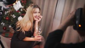 Το πρότυπο κορίτσι θέτει για το φωτογράφο, χαμογελά προκλητικό και εξετάζει αδιάφορα τη κάμερα Κρατά ένα ποτήρι του κρασιού σε δι φιλμ μικρού μήκους