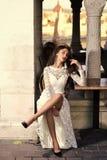 Το πρότυπο μόδας με τη γοητεία κοιτάζει και makeup Η προκλητική γυναίκα κάθεται μόνο στον καφέ οδών Γυναίκα στο άσπρο γαμήλιο φόρ στοκ φωτογραφία