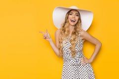 Το πρότυπο μόδας γέλιου στο άσπρο καπέλο ήλιων δείχνει Στοκ Εικόνες