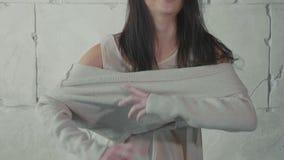 Το πρότυπο νεολαίας ντύνει επάνω το πουλόβερ πέρα από τον άσπρο τοίχο πετρών σε σε αργή κίνηση απόθεμα βίντεο