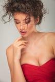 Το πρότυπο στο κόκκινο φόρεμα θέτει σχετικά με το πηγούνι της Στοκ εικόνα με δικαίωμα ελεύθερης χρήσης