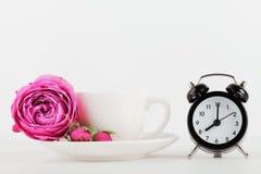 Το πρότυπο του φλυτζανιού καφέ με το ροδαλό λουλούδι και το ξυπνητήρι στο άσπρο γραφείο με το καθαρό διάστημα για το κείμενο και  Στοκ Εικόνα