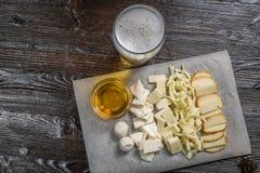 Το πρόχειρο φαγητό μπύρας του τυριού, με τη σάλτσα στην επιτροπή για την αρχειοθέτηση καλύπτεται με ένα φύλλο της περγαμηνής Στοκ εικόνες με δικαίωμα ελεύθερης χρήσης