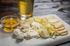 Το πρόχειρο φαγητό μπύρας του τυριού, με τη σάλτσα στην επιτροπή για την αρχειοθέτηση καλύπτεται με ένα φύλλο της περγαμηνής Στοκ εικόνα με δικαίωμα ελεύθερης χρήσης