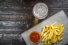 Το πρόχειρο φαγητό μπύρας των τηγανητών τηγανητών με το ζωμό στην επιτροπή για την αρχειοθέτηση καλύπτεται με ένα φύλλο της περγα Στοκ εικόνες με δικαίωμα ελεύθερης χρήσης