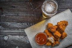 Το πρόχειρο φαγητό μπύρας των τηγανισμένων πασπαλισμένων με ψίχουλα κομματιών του κοτόπουλου με τη σάλτσα στην επιτροπή για την α Στοκ Φωτογραφίες