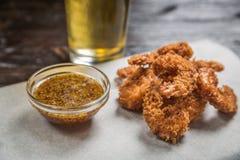 Το πρόχειρο φαγητό μπύρας των τηγανισμένων πασπαλισμένων με ψίχουλα κομματιών του κοτόπουλου με τη σάλτσα στην επιτροπή για την α Στοκ Εικόνες
