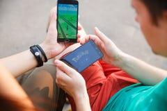 Το πρώτο κρατημένο άτομο τηλέφωνο στα χέρια που παρουσιάζουν οθόνη του με Pokemon πηγαίνει app, το δεύτερο εγκαθιστά εκείνη την ε Στοκ εικόνα με δικαίωμα ελεύθερης χρήσης