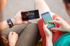 Το πρώτο κρατημένο άτομο τηλέφωνο στα χέρια που παρουσιάζουν οθόνη του με Pokemon πηγαίνει app, το δεύτερο εγκαθιστά εκείνη την ε Στοκ Εικόνες