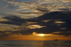 Το πρώτο φως πίσω από τη θάλασσα, που πλέει αν και ο ουρανός στοκ φωτογραφίες