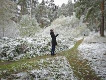 Το πρώτο χιόνι ενέπεσε στο χρυσό φθινόπωρο Το ευτυχές κορίτσι στα ξύλα στην πορεία χαίρεται στοκ εικόνες