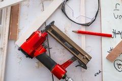Το πυροβόλο όπλο καρφιών στο βιομηχανικό κατάστημα επίπλων για τα έπιπλα χτίζει, εργαλεία ξυλουργικής στοκ φωτογραφίες