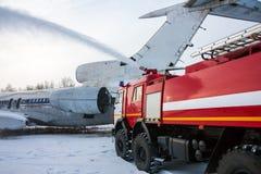 Το πυροσβεστικό όχημα αεροδρομίων εξαφανίζει τα αεροσκάφη μετά από τη αναγκαστική προσγείωση σε έναν κρύο καιρό Στοκ Φωτογραφία
