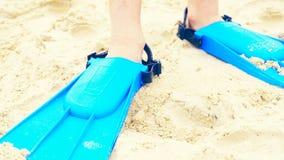 Το πόδι ενός μικρού αγοριού που φορά τα μπλε βατραχοπέδιλα για μαθαίνει να κολυμπά τη στάση στην άμμο παραλιών Οι διακοπές θερινώ στοκ εικόνες