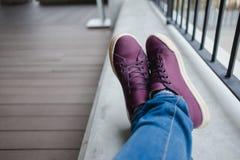 Το πόδι των γυναικών με Jean και τη συνεδρίαση παπουτσιών στο πάτωμα τσιμέντου πρέπει να επιζητήσει στοκ φωτογραφίες