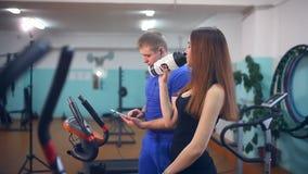 Το πόσιμο νερό αθλητών κοριτσιών παίρνει κουρασμένο στους αθλητικούς εκπαιδευτές γυμναστικής απόθεμα βίντεο