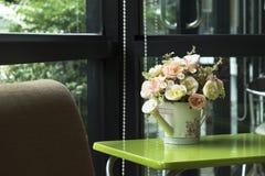 Το πότισμα διακοσμήσεων μπορεί με τα τεχνητά λουλούδια στο ασβέστιο καφέ Στοκ φωτογραφία με δικαίωμα ελεύθερης χρήσης