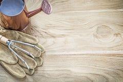 Το πότισμα μπορεί μέταλλο να μαζεψει με τη τσουγκράνα τα γάντια κηπουρικής στο ξύλινο αντίγραφο πινάκων spac Στοκ εικόνες με δικαίωμα ελεύθερης χρήσης