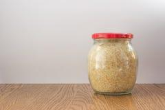 Το πλήρες βάζο γυαλιού με το ρύζι έκλεισε την κόκκινη ΚΑΠ σε ξύλινο Στοκ φωτογραφία με δικαίωμα ελεύθερης χρήσης