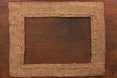 Το πλαίσιο burlap, βρίσκεται σε ένα υπόβαθρο του ξύλου Στοκ Εικόνα