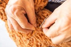 Το ράψιμο γυναικών teddy αντέχει, βελτιώνει μια σπασμένη κούκλα Στοκ Εικόνες