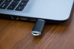 Το ραβδί μνήμης USB ή η κίνηση λάμψης συνδέθηκε με την πλευρά ενός lap-top Στοκ Εικόνες