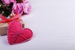 Το ροζ αισθάνθηκε την καρδιά, τα λουλούδια και το χειροποίητο δώρο σε έναν άσπρο ξύλινο πίνακα, έννοια, έμβλημα, εκτός από το διά στοκ φωτογραφία