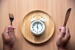 Το ρολόι είναι το μεσημέρι 12:00 για το μεσημεριανό γεύμα σε ένα ξύλινο πιάτο στοκ φωτογραφίες