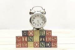 Το ρολόι με τους ξύλινους κύβους στις ξύλινες ώρες επιτραπέζιων λέξεων, πρακτικά, δευτερόλεπτα δροσίζει Στοκ Εικόνα