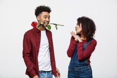Το ρομαντικό άτομο αφροαμερικάνων ερωτευμένο, κρατώντας αυξήθηκε μεταξύ των δοντιών του που στέκονται μπροστά από τη φίλη του στοκ φωτογραφίες με δικαίωμα ελεύθερης χρήσης