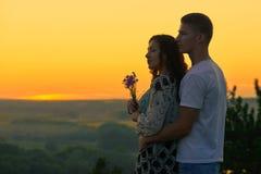 Το ρομαντικό ζεύγος κοιτάζει στο ηλιοβασίλεμα στο υπαίθριο, όμορφο τοπίο χωρών και το φωτεινό κίτρινο ουρανό, έννοια τρυφερότητας Στοκ Φωτογραφία