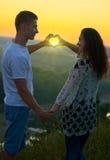 Το ρομαντικό ζεύγος στο ηλιοβασίλεμα κάνει μια μορφή καρδιών από τα χέρια, οι ακτίνες λάμπουν μέσω των χεριών, όμορφο τοπίο και φ Στοκ Εικόνες