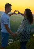 Το ρομαντικό ζεύγος στο ηλιοβασίλεμα παρουσιάζει μορφή καρδιών από τα χέρια, το όμορφο τοπίο και το φωτεινό κίτρινο ουρανό, έννοι Στοκ Φωτογραφίες