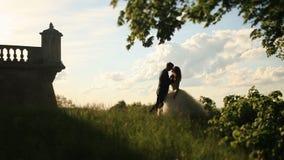 Το ρομαντικό φιλί το ζεύγος στο πάρκο ηλιοβασιλέματος κοντά στο εκλεκτής ποιότητας κτήριο με το κιγκλίδωμα απόθεμα βίντεο