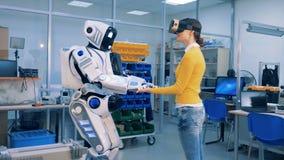 Το ρομποτικό humanoid βάζει τα χέρια του επάνω στα χέρια μιας νέας γυναίκας απόθεμα βίντεο