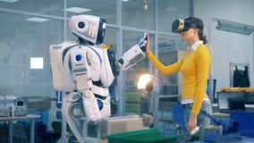 Το ρομποτικό humanoid κάνει υψηλός-πέντε σε μια κυρία στα γυαλιά εικονικής πραγματικότητας απόθεμα βίντεο