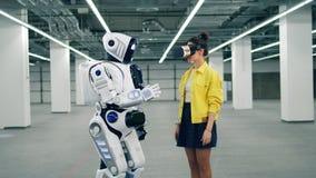 Το ρομπότ αγγίζει ένα χέρι μιας κυρίας στα VR-γυαλιά απόθεμα βίντεο