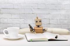 Το ρομπότ κάθεται στον πίνακα, θέση εργασίας: ημερολόγιο, μάνδρες, φλυτζάνια στοκ εικόνες